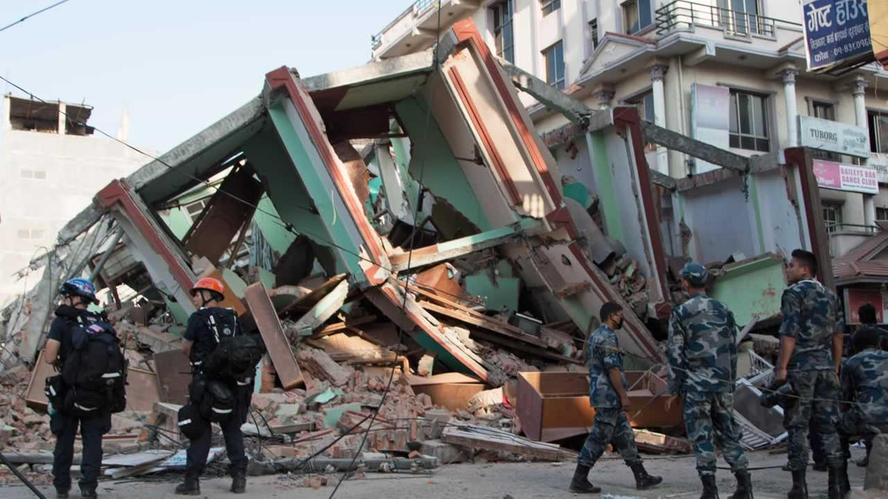 Rescue workers stand beside a building that collapsed in an earthquake in Kathmandu, Nepal, Tuesday, May 12, 2015.