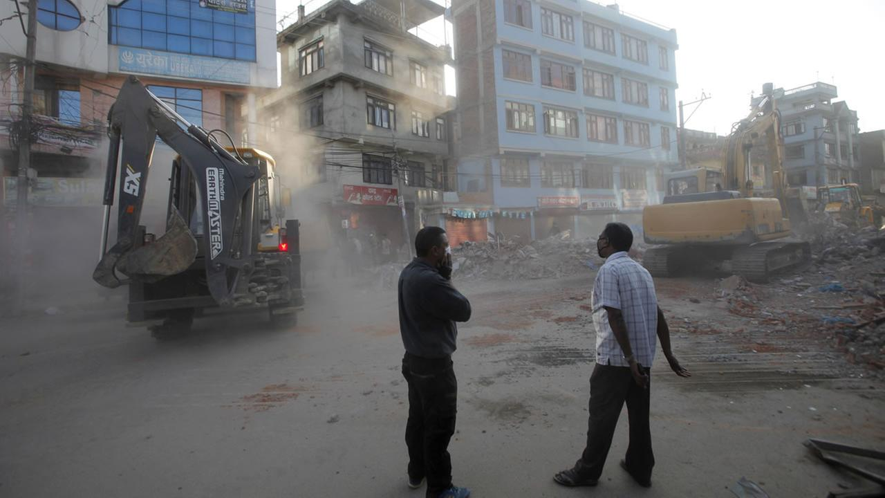 Dust rises as earth movers clear debris from damage caused by an earthquake in Kathmandu, Nepal, Tuesday, May 12, 2015.AP Photo/Bikram Rai