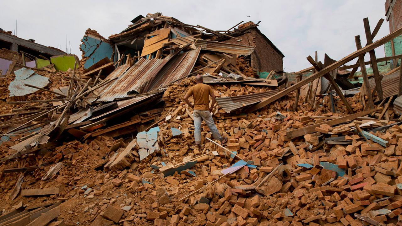 A man inspects an area that collapsed during the May 12 earthquake in Chautara, Nepal, Wednesday, May 13, 2015.
