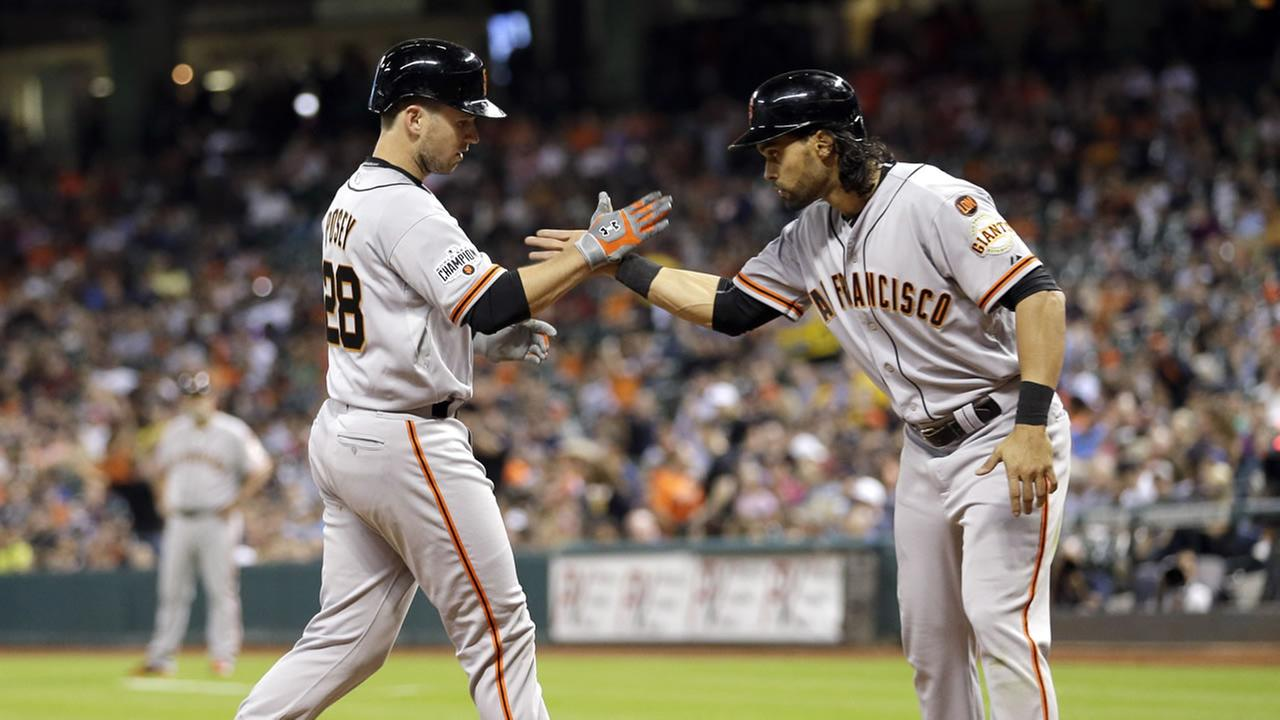 San Francisco Giants Buster Posey (28) is congratulated by Angel Pagan after both scored on Poseys home run against the Houston Astros during the fifth inning of a baseball game.