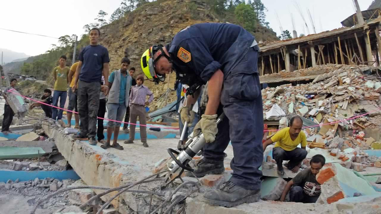 In this May 12, 2015 photo, a member of the Fairfax County Fire and Rescue Departments team helps rescue a woman from a four-story building that collapsed in Singati, Nepal.