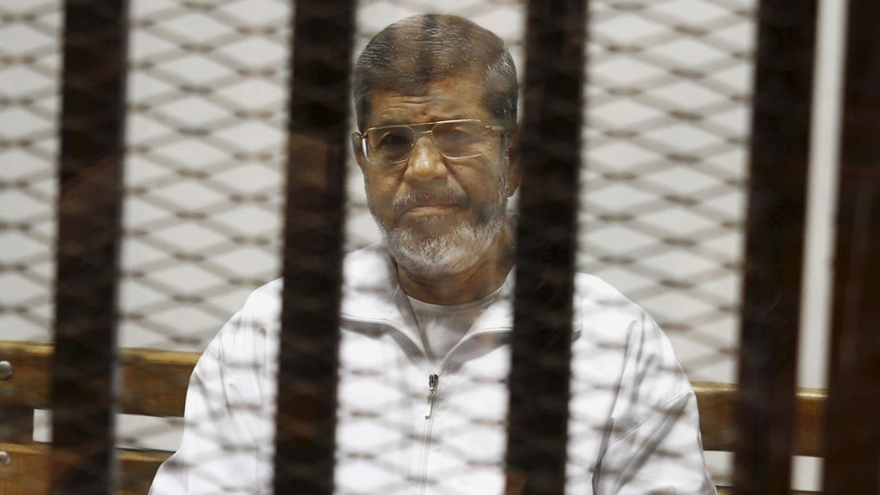 In this May 8, 2014 file photo, Egypts ousted Islamist President Mohammed Morsi sits in a defendant cage in the Police Academy courthouse in Cairo, Egypt.