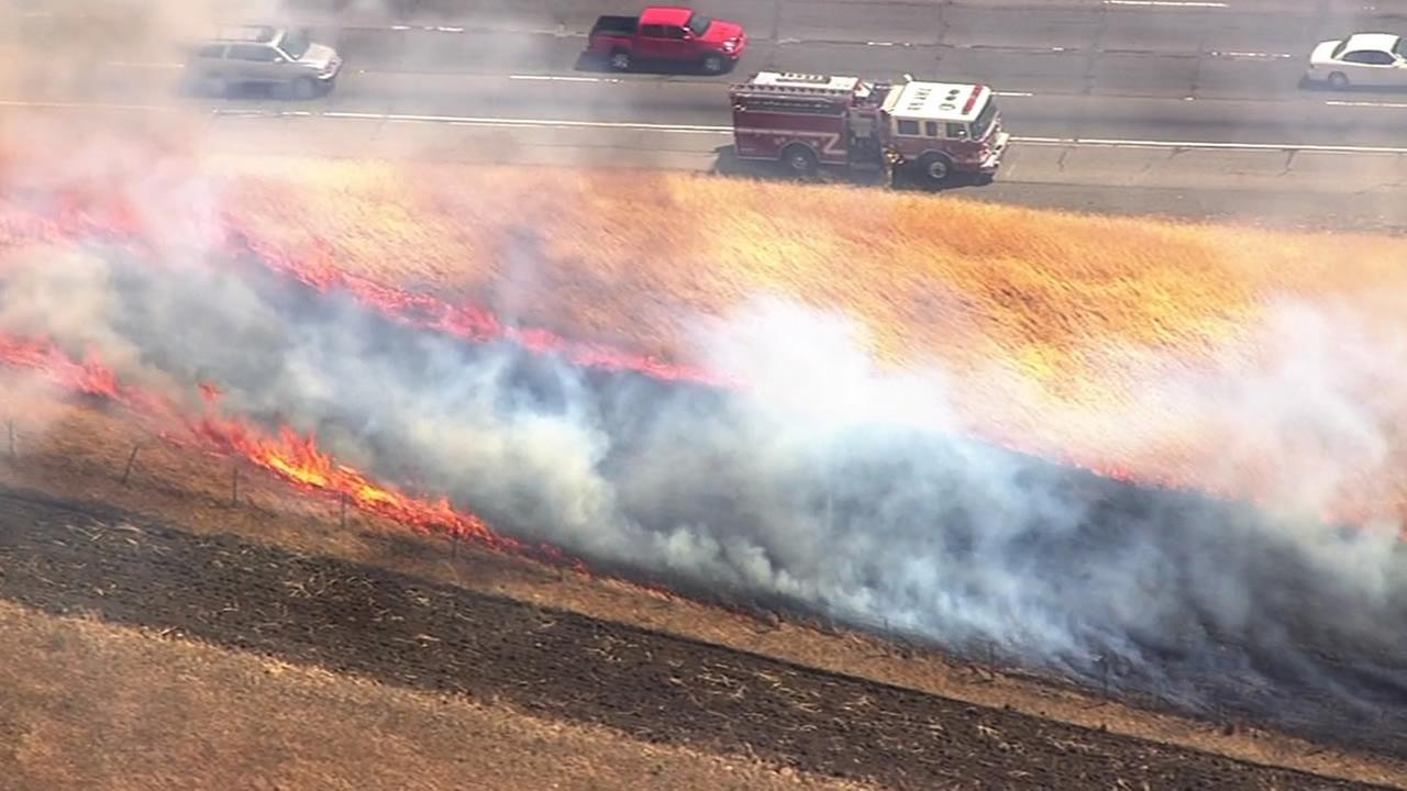 Crews are battling a brush fire along Interstate 580 in the Altamont Pass area in Alameda County