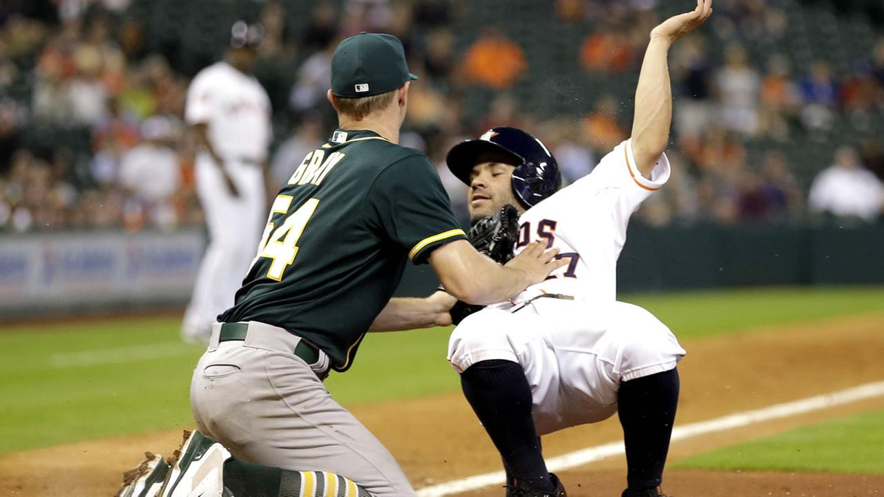 Houston Astros Jose Altuve (27) is tagged out by Oakland Athletics starting pitcher Sonny Gray (54) while trying to score during the fifth inning of a baseball game May 19, 2015.