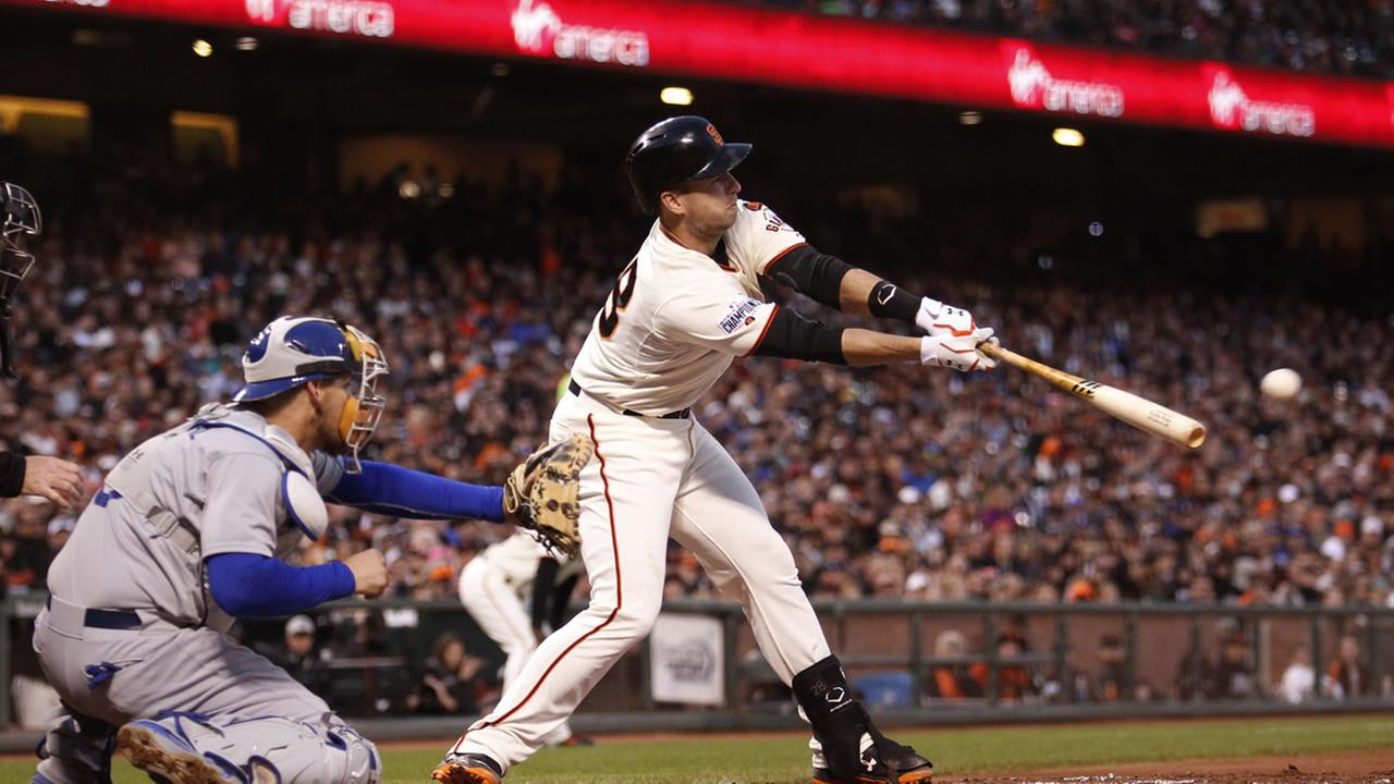 San Francisco Giants Buster Posey hits an RBI single to score Joe Panik during the third inning of a baseball game against the Los Angeles Dodgers, Tuesday, May 19, 2015.