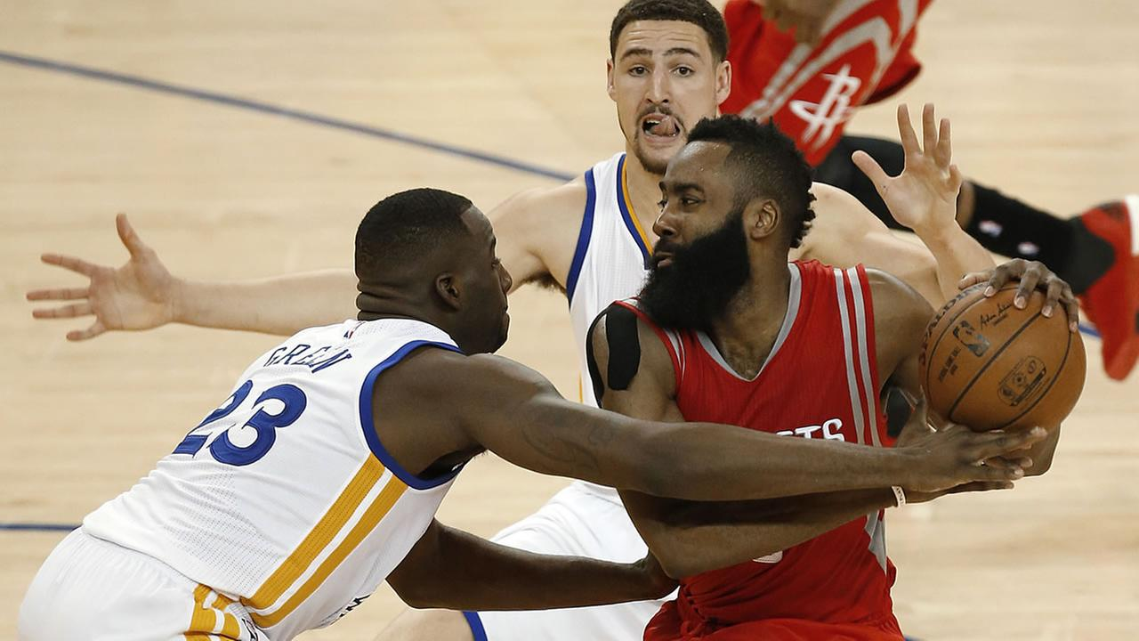 Houston Rockets guard James Harden, right, is defended by Golden State Warriors forward Draymond Green (23) and guard Klay Thompson during the second half of Game 2.AP Photo/Tony Avelar