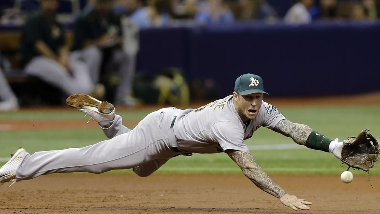 Oakland Athletics third baseman Brett Lawrie makes a diving stop on a ground ball by Tampa Bay Rays Bobby Wilson during the third inning of a baseball game Thursday, May 21, 2015.