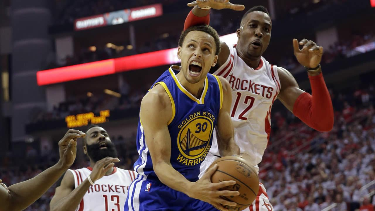 Warriors Stephen Curry looks toward the basket before being fouled by Rockets Dwight Howard during the first half in Game 3 of the NBA basketball Western Conference finals on May 23, 2015, in Houston. (AP Photo)