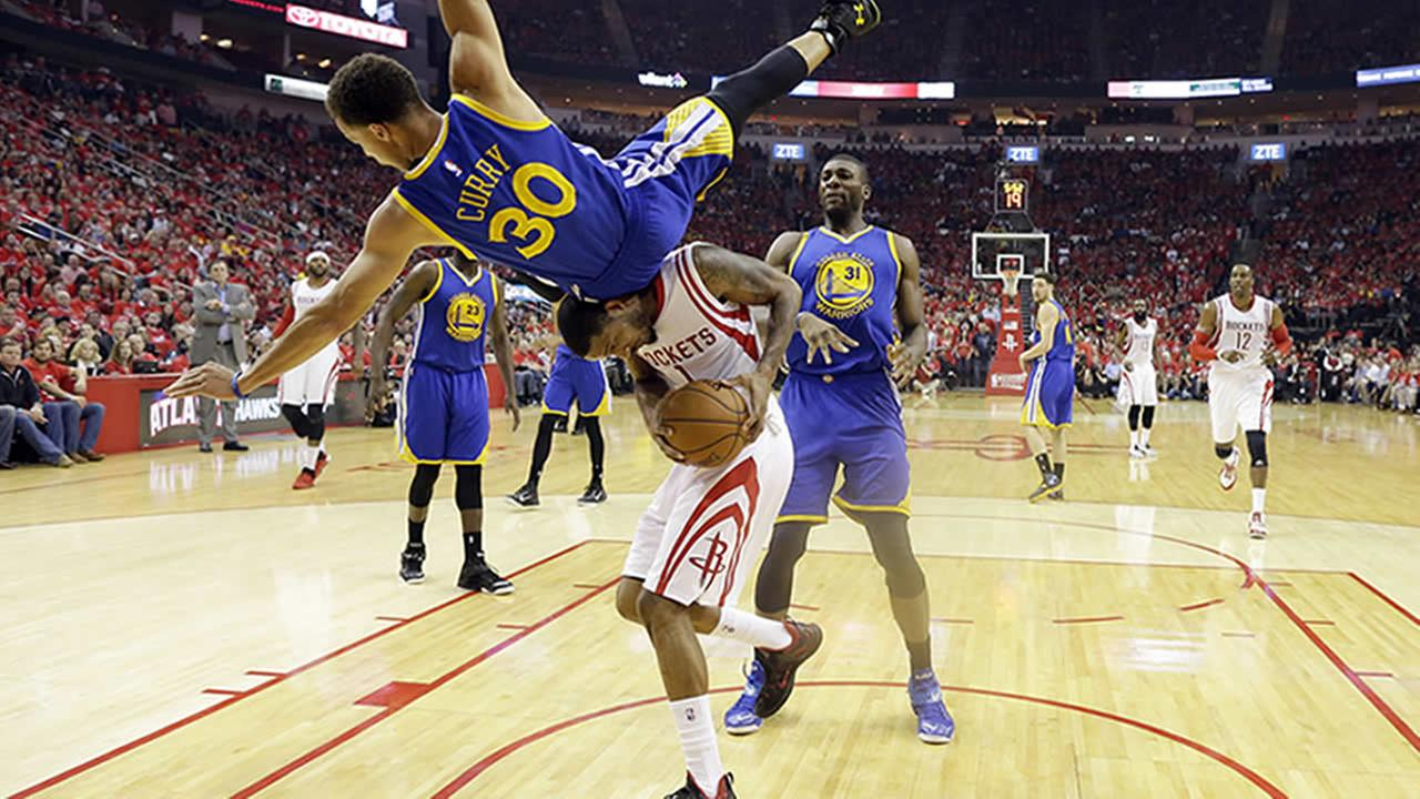 Golden State Warriors guard Stephen Curry topples over Houston Rockets forward Trevor Ariza