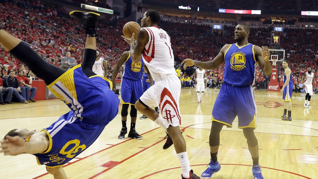 Golden State Warriors guard Stephen Curry (30) topples over Houston Rockets forward Trevor Ariza (1) during the first half in Game 4 of the Western Conference finals in Houston.