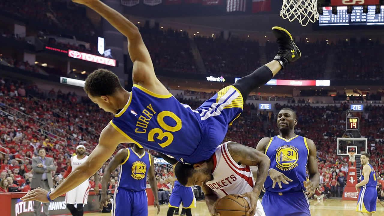 Warriors guard Stephen Curry topples over Rockets forward Trevor Ariza during Game 4 of the Western Conference finals of the NBA basketball playoffs, May 25, 2015, in Houston. (AP Photo/David J. Phillip)