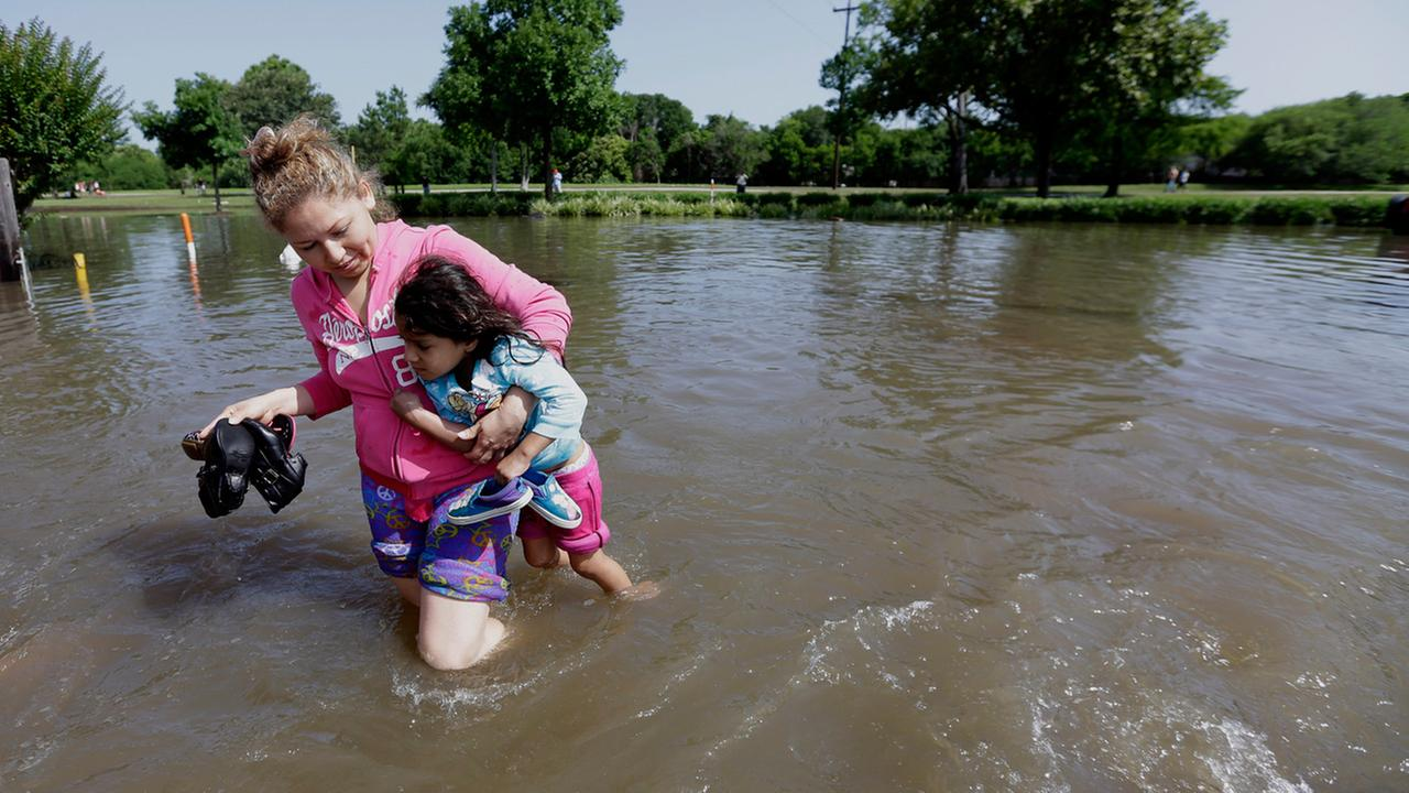 Nayeli Cervantes carries her friends daughter Sophia Aviles through the floodwaters outside their apartment in Houston, Tuesday, May 26, 2015.