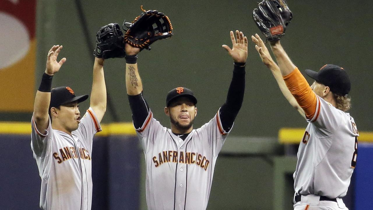 San Francisco Giants Nori Aoki, left to right, Gregor Blanco and Hunter Pence celebrate after a baseball game against the Milwaukee Brewers Tuesday, May 26, 2015, in Milwaukee.