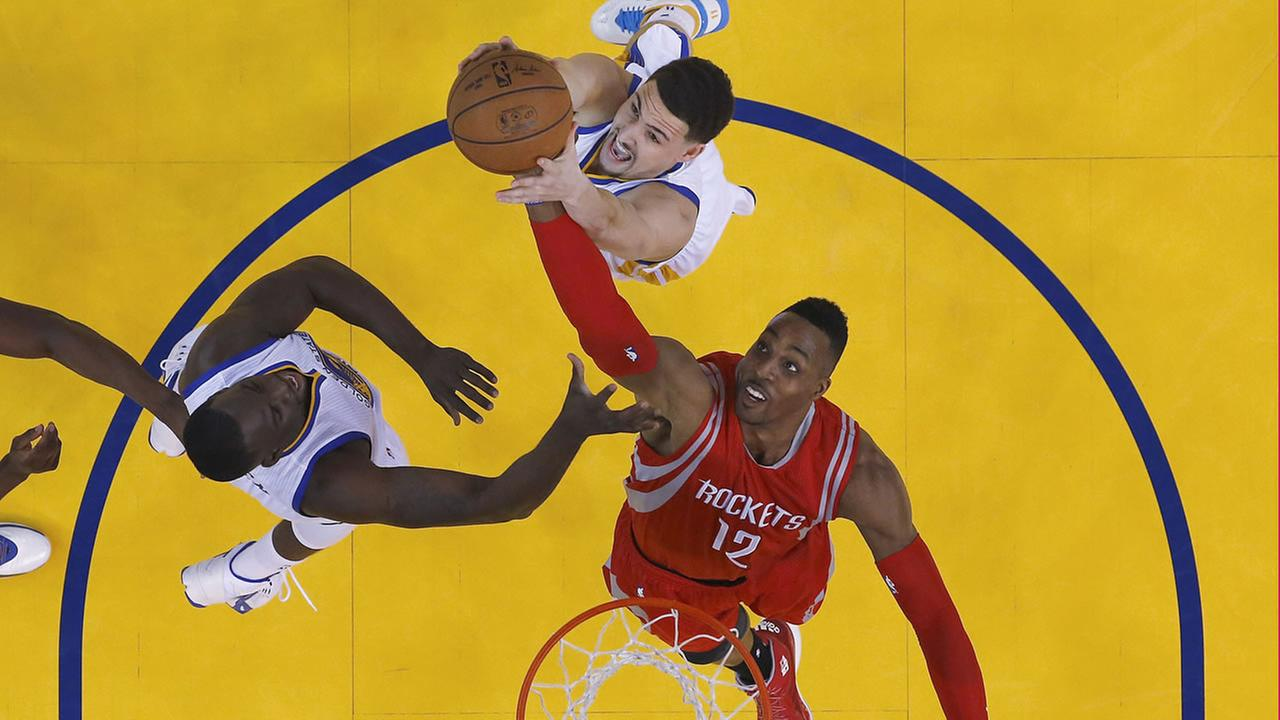 Houston Rockets center Dwight Howard (12) reaches for a rebound between Golden State Warriors guard Klay Thompson, top, and forward Draymond Green during the first half of Game 5.