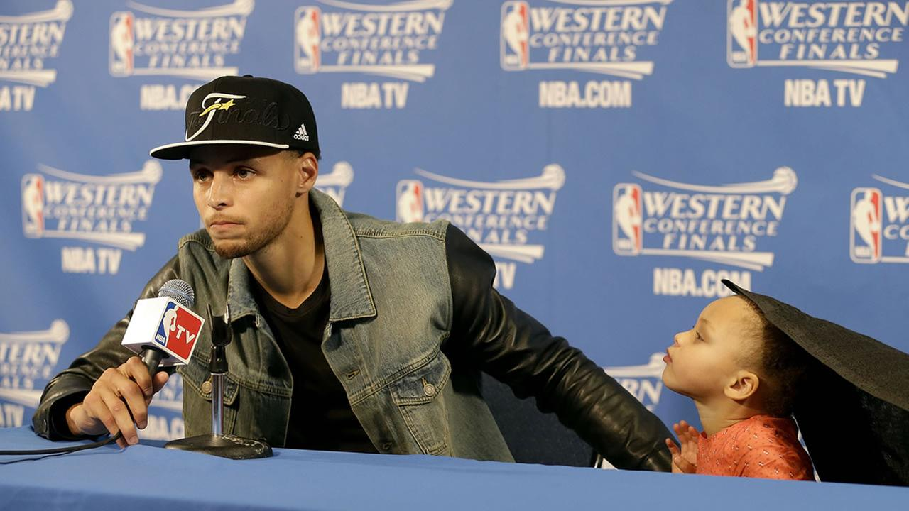Golden State Warriors guard Stephen Curry speaks with his daughter Riley at his side during a news conference after Game 5 of the NBA basketball Western Conference finals.AP Photo/Tony Avelar