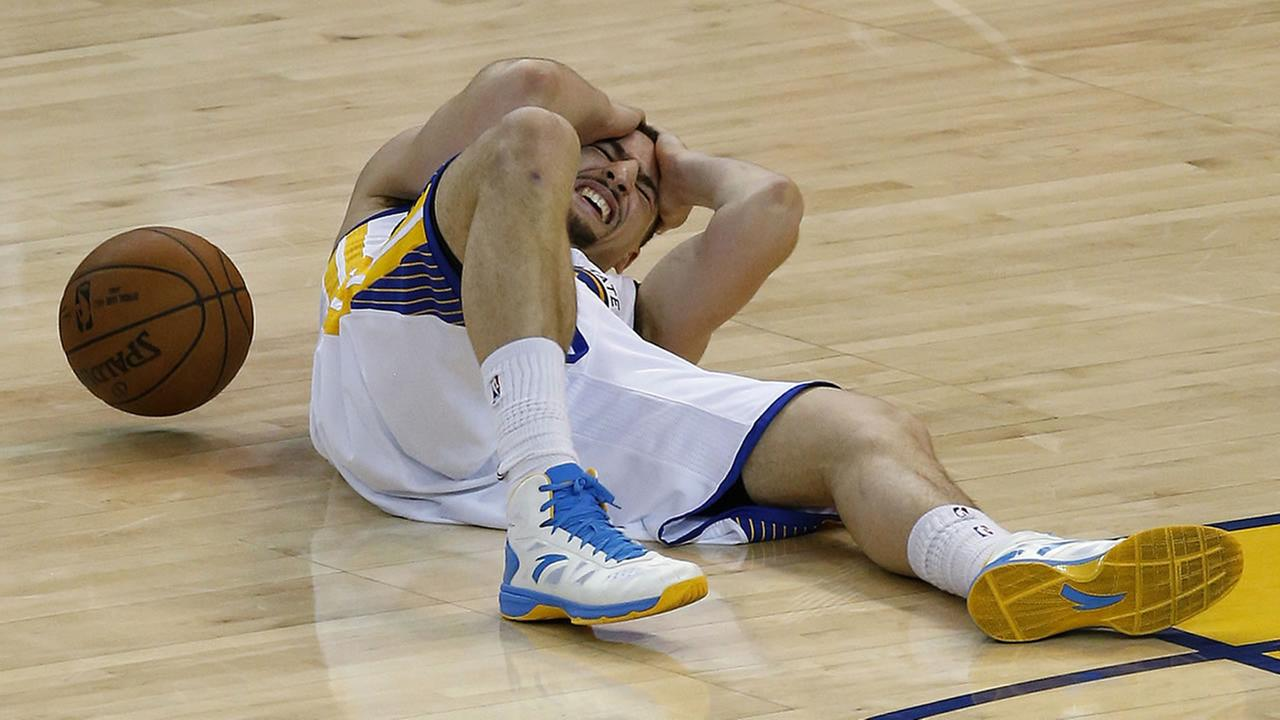 Warriors guard Klay Thompson lies on the court after being injured during the second half of Game 5 of the NBA basketball Western Conference finals on Wednesday, May 27, 2015.