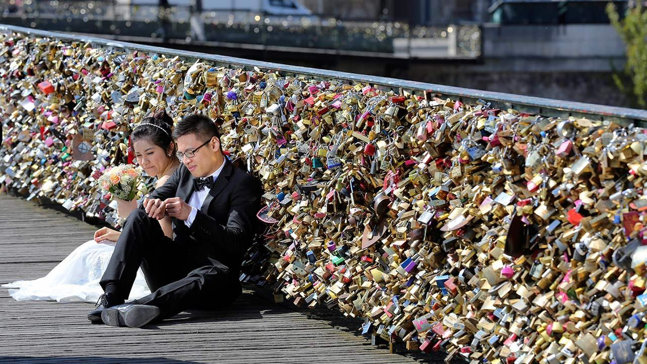 This Wednesday April 16, 2014 file photo shows a newlywed couple resting on the famed Pont des Arts in Paris, France. (AP Photo)
