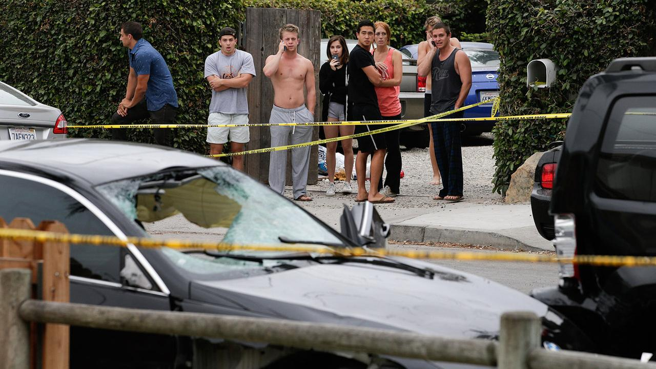 People look at a black BMW sedan driven by a drive-by shooter on Saturday, May 24, 2014, in Isla Vista, Calif.