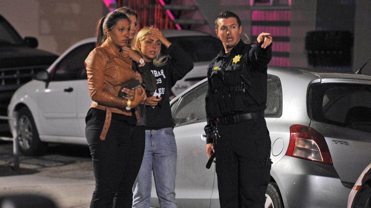 In this image provided by the Santa Barbara Independent, people speak to a police officer after a mass shooting near the campus of the University of Santa Barbara in Isla Vista, Calif., Friday, May 23, 2014.