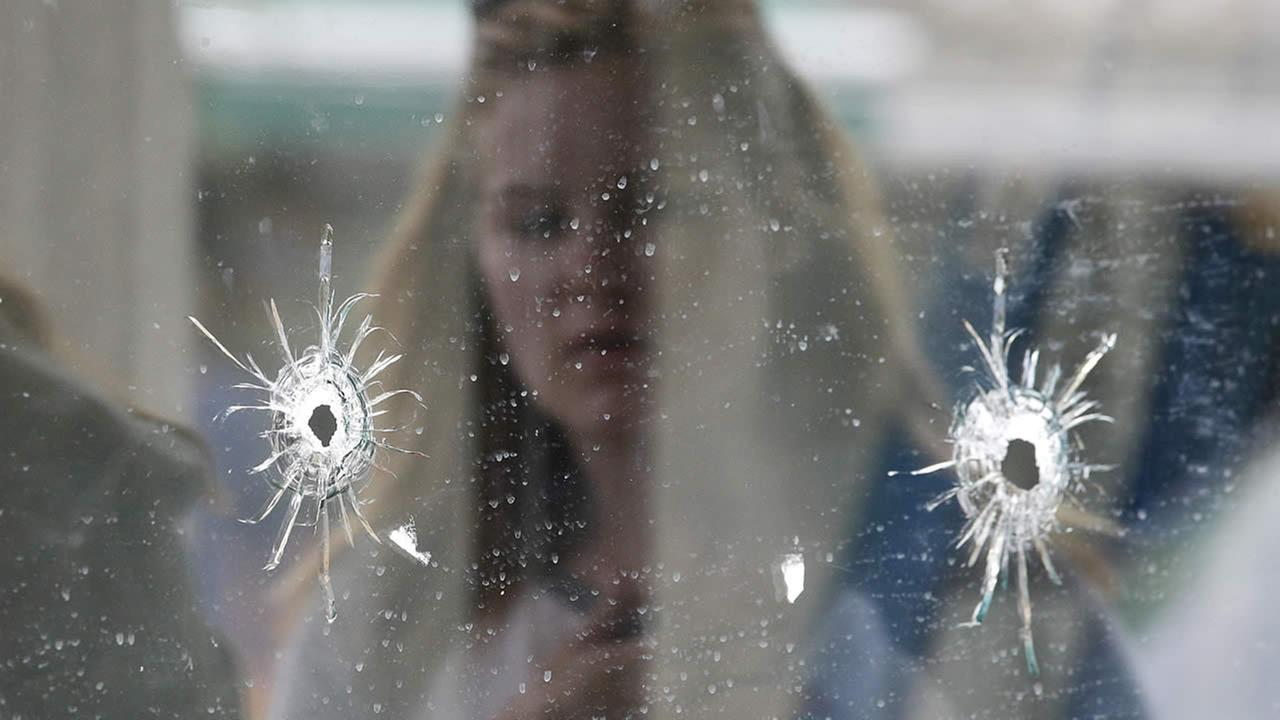 A woman looks at the bullet holes on the window of IV Deli Mark where Friday nights mass shooting took place by a drive-by shooter on Saturday, May 24, 2014(AP Photo/Jae C. Hong)