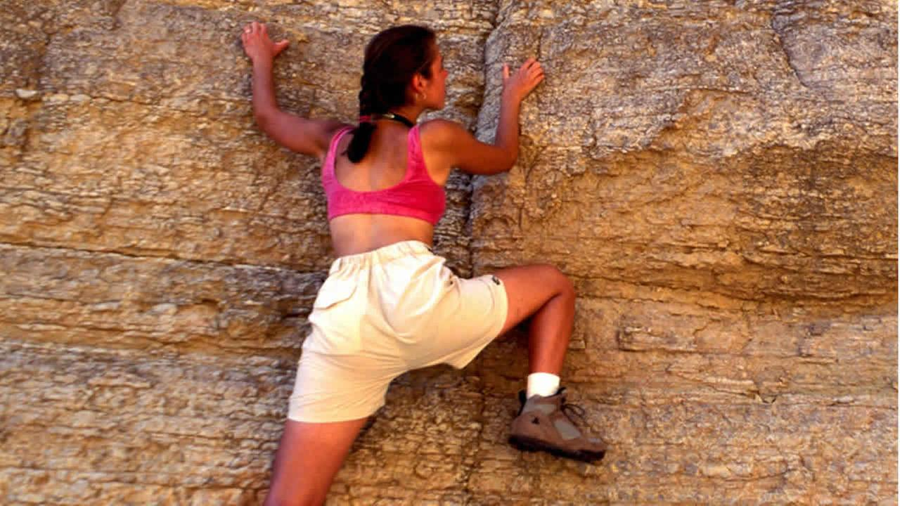 Woman climbing a mountain.