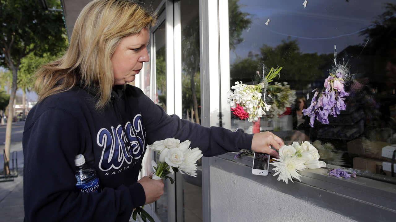 Jennifer Peake places flowers by the window of IV Deli Mart, where part of a mass shooting took place on Saturday, May 24, 2014, in Isla Vista, Calif. (AP Photo/Jae C. Hong)