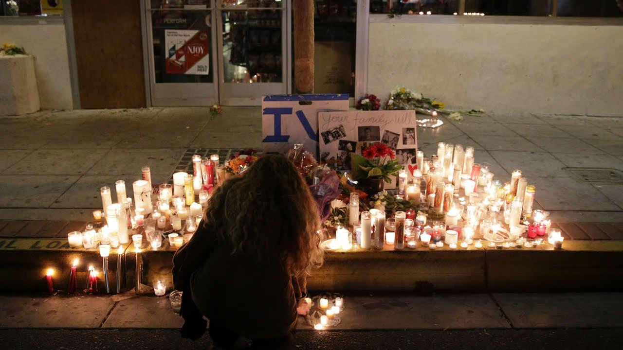 A woman places a candle in front of IV Deli Mart, where part of a mass shooting took place on May 24, 2014, in the beach community of Isla Vista, Calif. (AP Photo/Jae C. Hong)