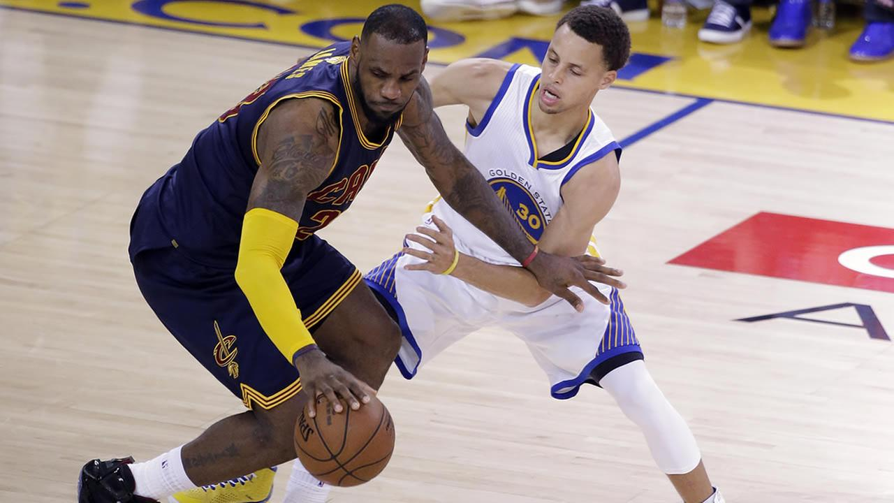Cavaliers forward LeBron James, left, is guarded by Warriors guard Stephen Curry during the second half of Game 2 of basketballs NBA Finals in Oakland, Calif., June 7, 2015. (AP Photo/Eric Risberg)