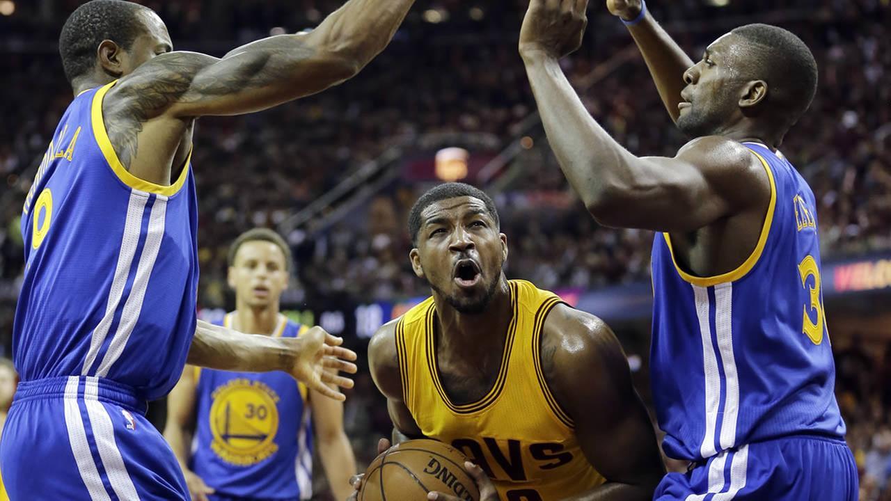 Cavaliers center Tristan Thompson looks to shoot between Warriors Andre Iguodala and Festus Ezeli