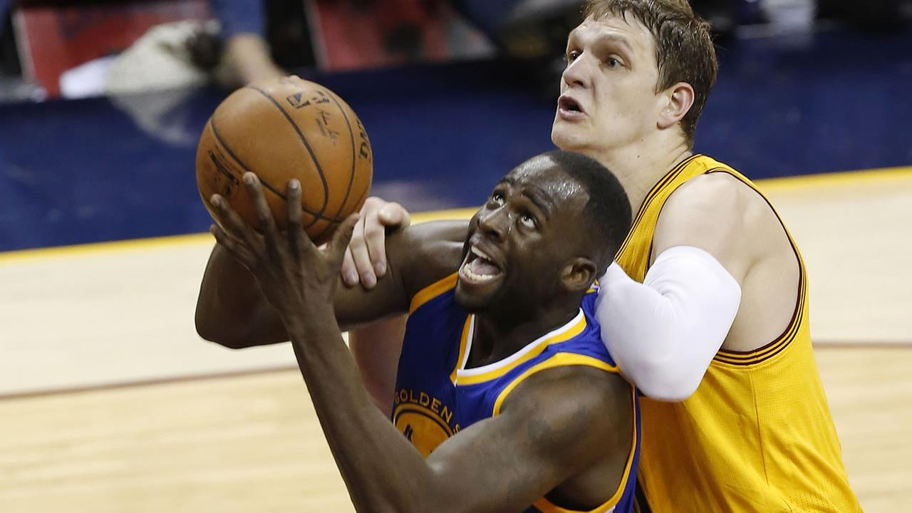 Warriors forward Draymond Green, left, is fouled by Cleveland Cavaliers center Timofey Mozgov during the first half of Game 3 of the NBA Finals in Cleveland, Tuesday, June 9, 2015.