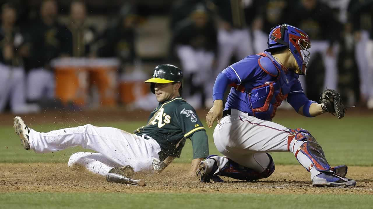 Athletics Sam Fuld, left, slides to score behind Texas Rangers catcher Robinson Chirinos in the ninth inning of a baseball game Wednesday, June 10, 2015, in Oakland, Calif.