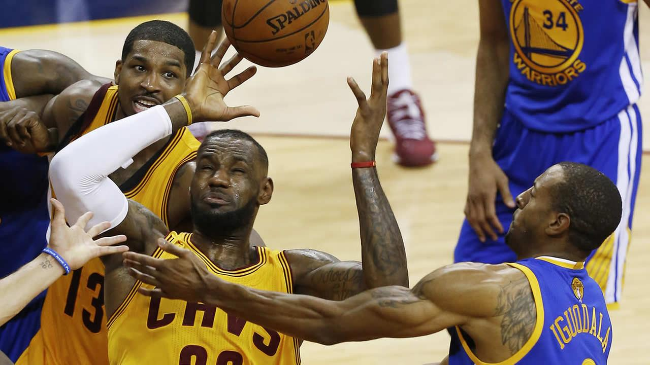 Cavaliers forward LeBron James tries to grab a rebound over Warriors guard Andre Iguodala during the second half of Game 4 of basketballs NBA Finals in Cleveland, June 11, 2015. (AP Photo/Paul Sancya)