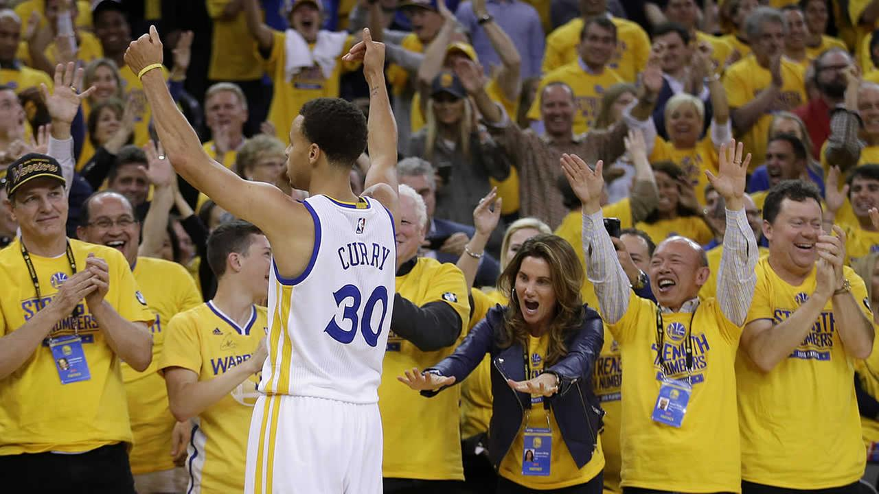 Fans cheer Golden State Warriors guard Stephen Curry during the NBA basketball Western Conference finals against the Houston Rockets in Oakland, Calif., May 21, 2015. (AP Photo/Rick Bowmer)