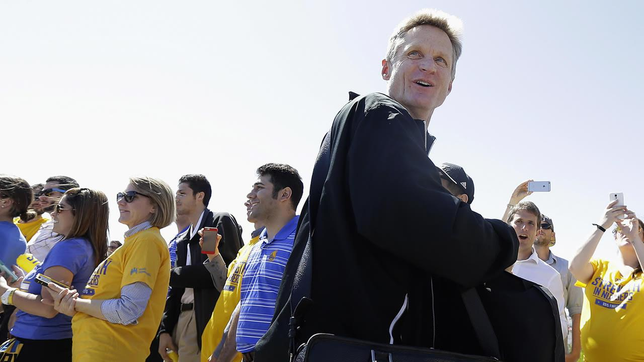 Golden State Warriors head coach Steve Kerr smiles as he walks past team employees after the team landed in Oakland, Calif., Wednesday, June 17, 2015. (AP Photo/Jeff Chiu)AP Photo/Jeff Chiu