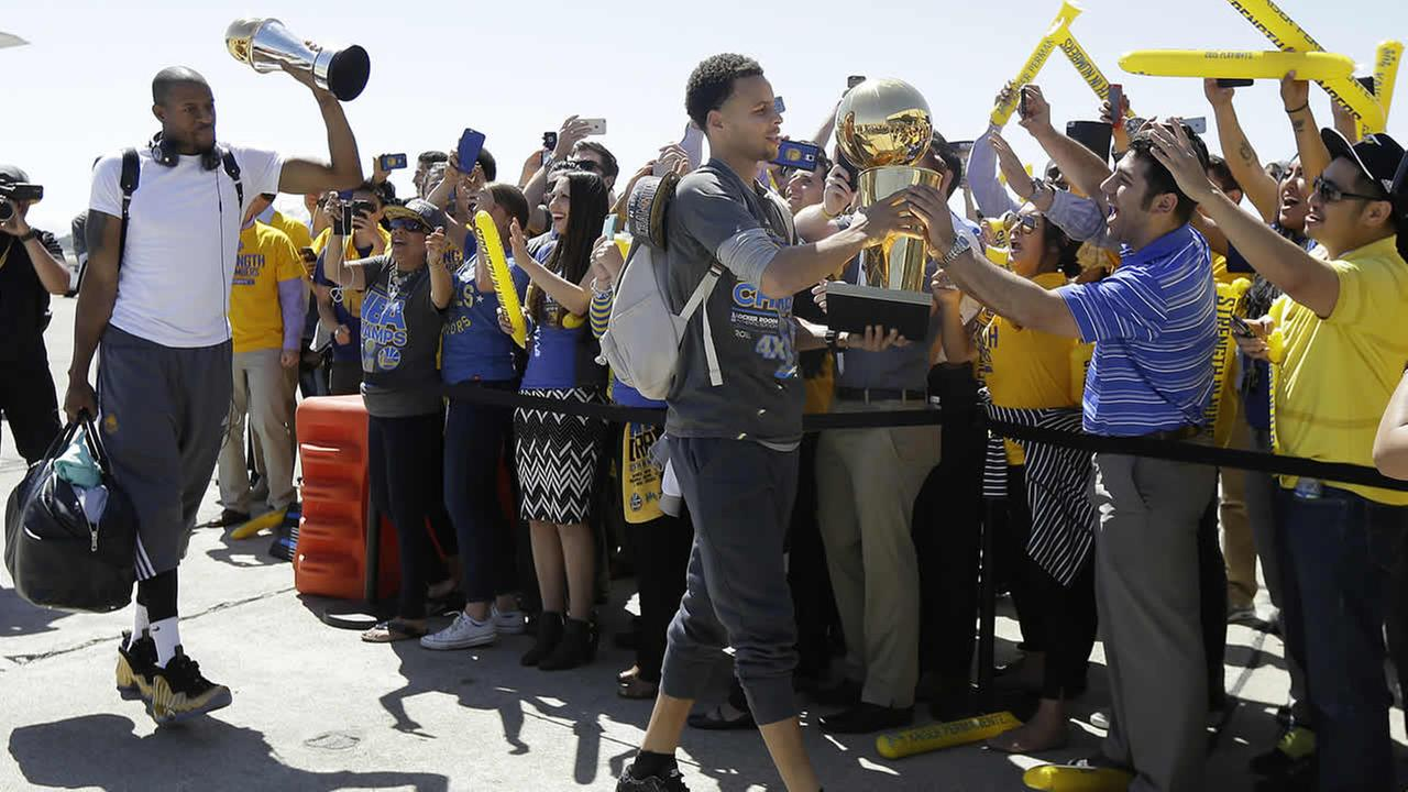 Warriors guard Stephen Curry carries the championship trophy in front of Andre Iguodala after the team landed in Oakland, Calif., June 17, 2015. (AP Photo/Jeff Chiu)