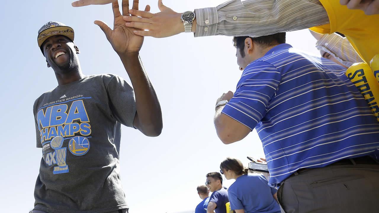 Golden State Warriors forward Draymond Green, left, high fives team employees after the team landed in Oakland, Calif., June 17, 2015. (AP Photo/Jeff Chiu)AP Photo/Jeff Chiu