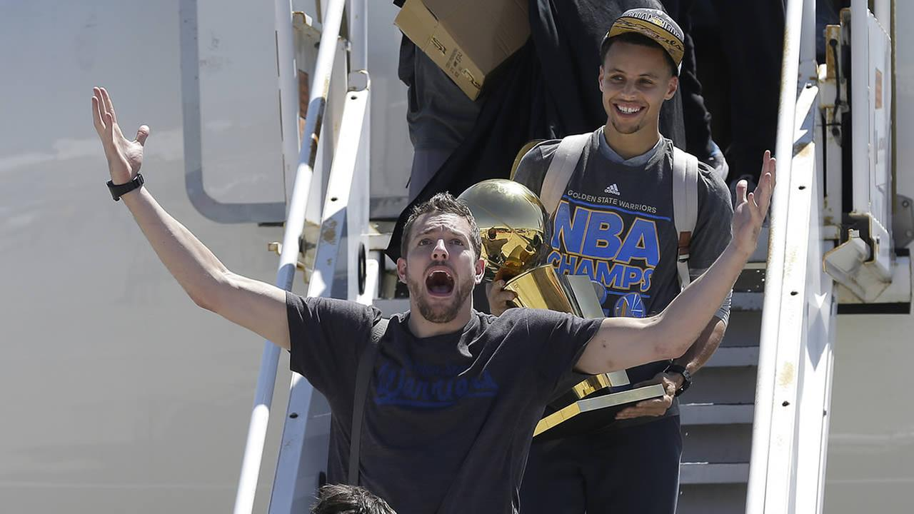 Warriors guard Stephen Curry carries the Larry OBrien championship trophy behind David Lee after the team landed in Oakland, Calif., June 17, 2015. (AP Photo/Jeff Chiu)