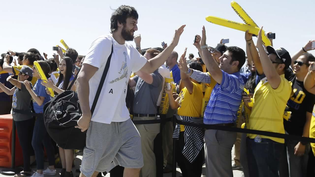 Golden State Warriors center Andrew Bogut greets team employees after the teams flight landed in Oakland, Calif., June 17, 2015. (AP Photo/Jeff Chiu) AP Photo/Jeff Chiu