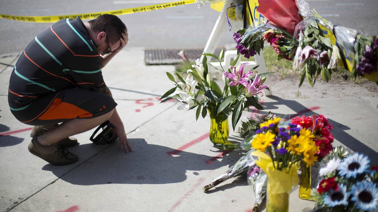 Noah Nicolaisen, of Charleston, S.C., kneels at a makeshift memorial, Thursday, June 18, 2015, down the street from the Emanuel AME Church.