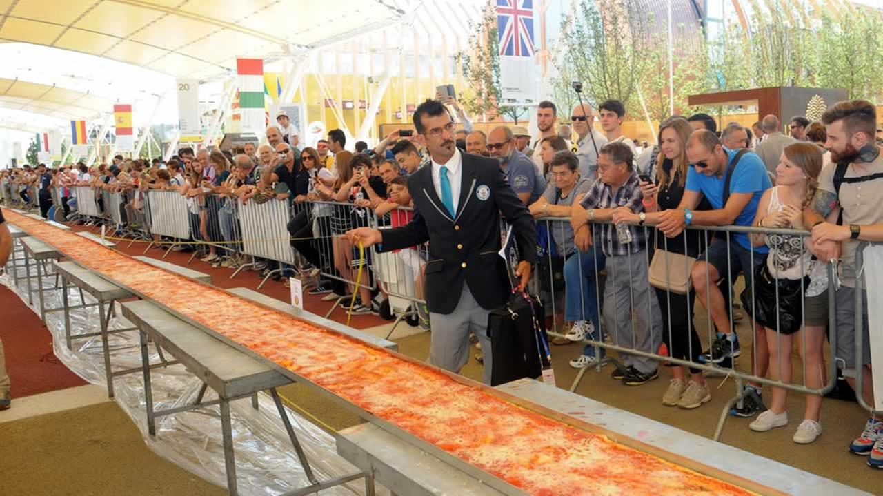 Judge of the Guinness World Records Lorenzo Veltri checks the length of a pizza at the Expo 2015 worlds fair in Rho, near Milan, Saturday, June 20, 2015.