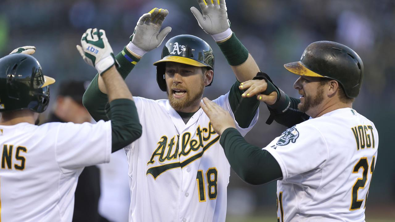 Athletics Ben Zobrist is congratulated by Billy Burns after Zobrist hit a three run home run off Angels Shoemaker during a game on Friday, June 19, 2015, in Oakland. (AP Photo)