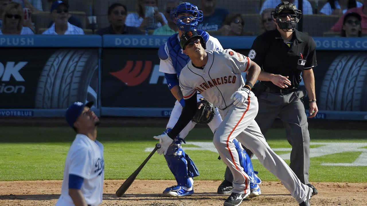 Giants Justin Maxwell hits a two-run home run as Dodgers Carlos Frias and catcher Yasmani Grandal watch during a game on June 20, 2015, in Los Angeles. (AP Photo/Mark J. Terrill)