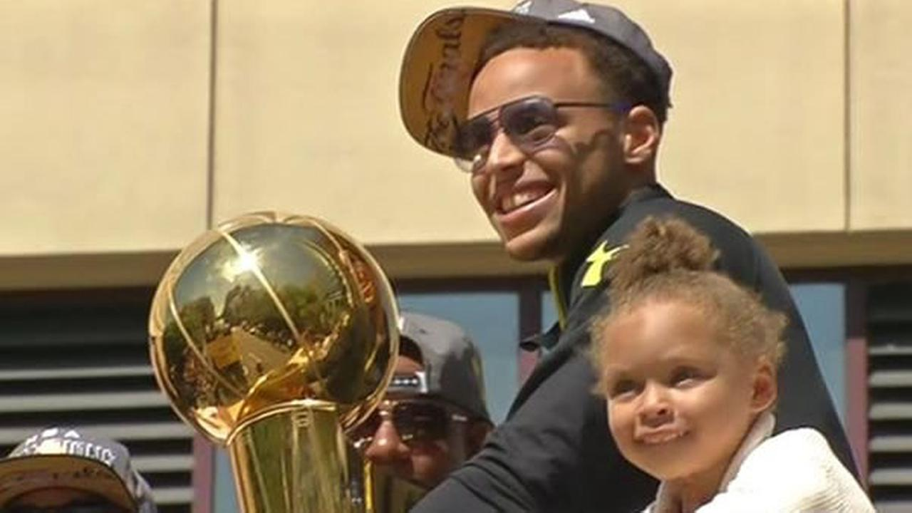 Golden State Warriors Steph Curry and daughter Riley ride a float during the teams victory parade on Friday, June 19, 2015 in Oakland, Calif.