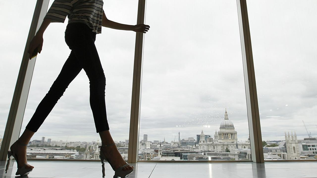 In this Sunday, Sept. 16, 2012 file photo, a model walks past a window with a view of St. Pauls Cathedral during London Fashion Week.