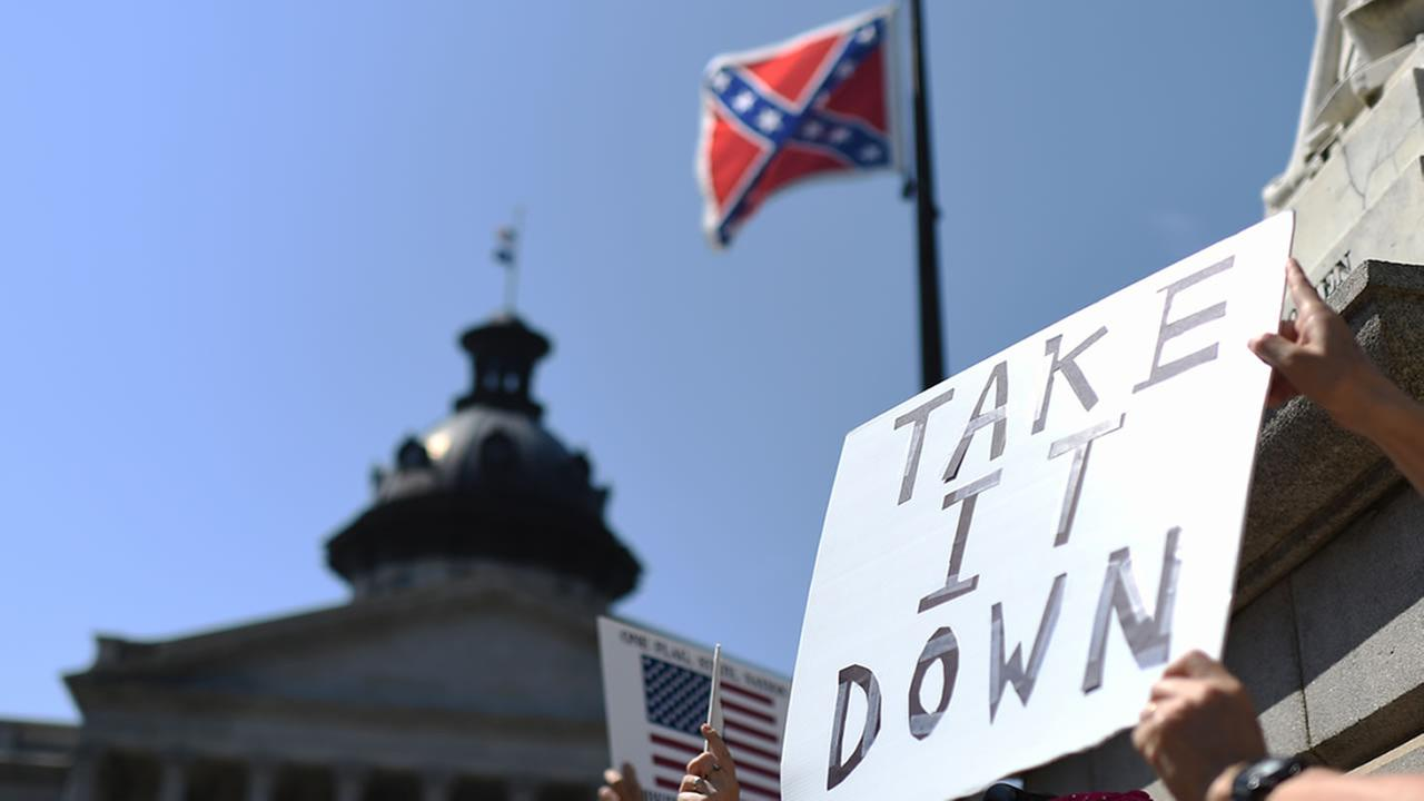 Protesters hold a sign during a rally to take down the Confederate flag at the South Carolina Statehouse, Tuesday, June 23, 2015, in Columbia, S.C.