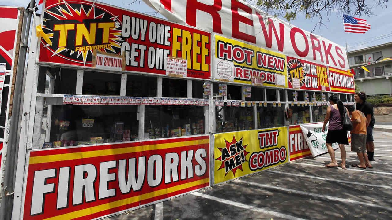 A family buys fireworks at a TNT Fireworks stand in the City of Monterey Park, Calif., on July 2, 2013.  (AP Photo/Nick Ut)