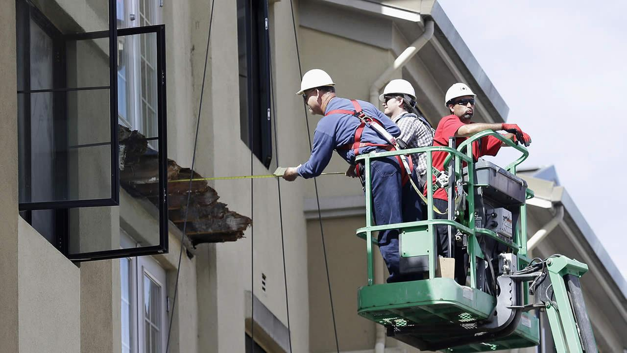 FILE- In this Wednesday, June 17, 2015 file photo, a worker measures near the remaining wood from an apartment building balcony that collapsed in Berkeley, Calif.  (AP Photo)