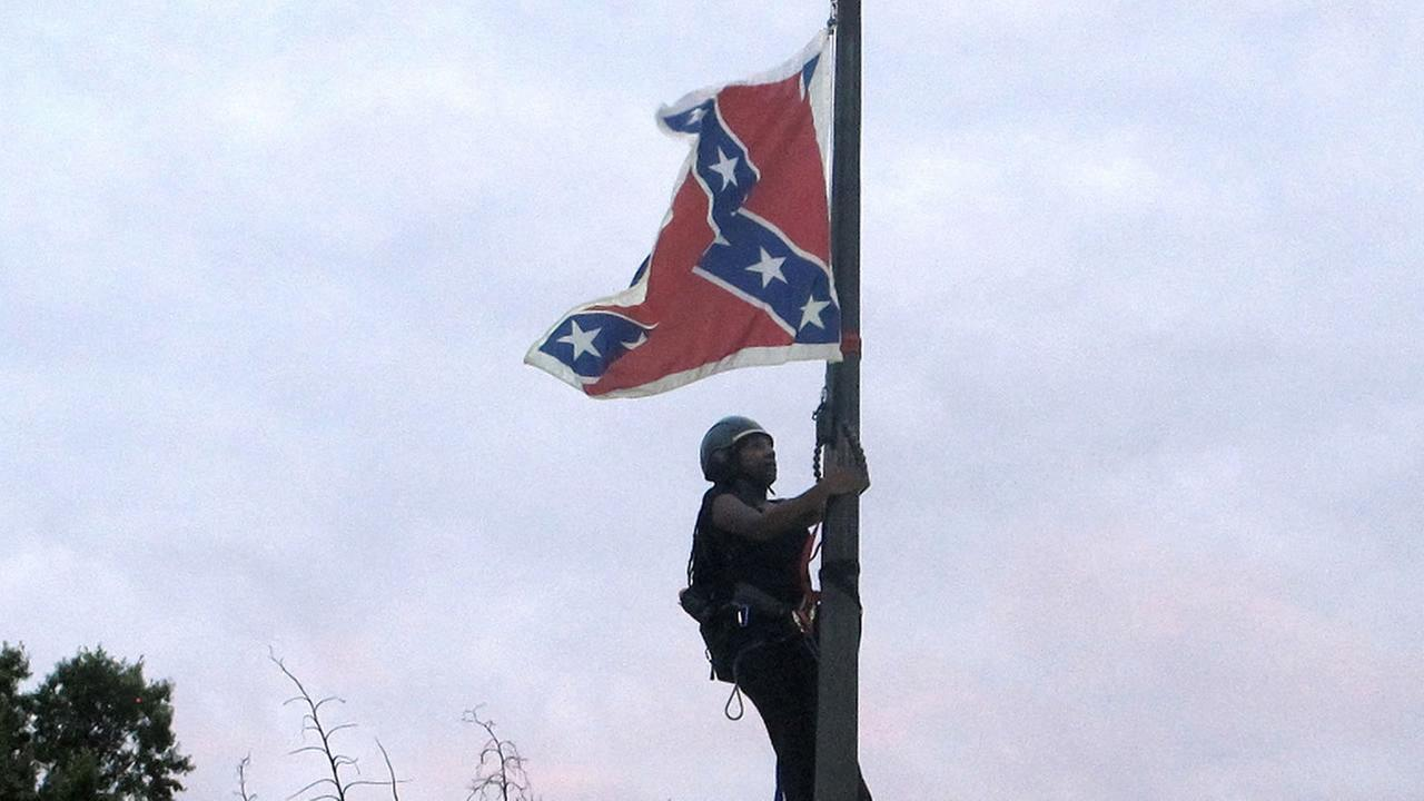 Bree Newsome climbs a flagpole to remove the Confederate battle flag at a Confederate monument in front of the Statehouse in Columbia, S.C., on Saturday, June, 27, 2015.