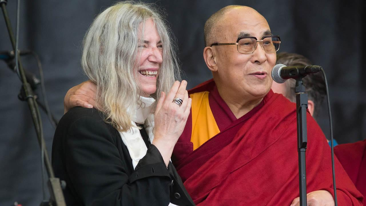The Dalai Lama speaks to the crowd during singer Patti Smiths, left, performance at the Glastonbury music festival on Sunday, June 28, 2015 at Worthy Farm, Glastonbury, England. (Photo by Jim Ross/Invision/AP)