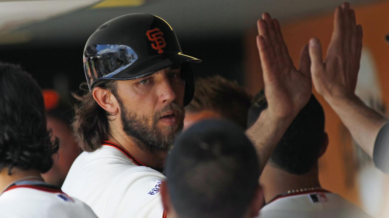 San Francisco Giants Madison Bumgarner gets high fives in the dugout after scoring against the Colorado Rockies on June 28, 2015, in San Francisco. (AP Photo/George Nikitin)
